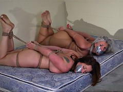 Two nude girls hogtied, toetied on mattress
