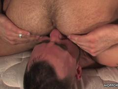 Hairy muscular men having sex on a bed