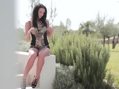 A bimbo with dark hair is outdoors, caressing her amazing curves